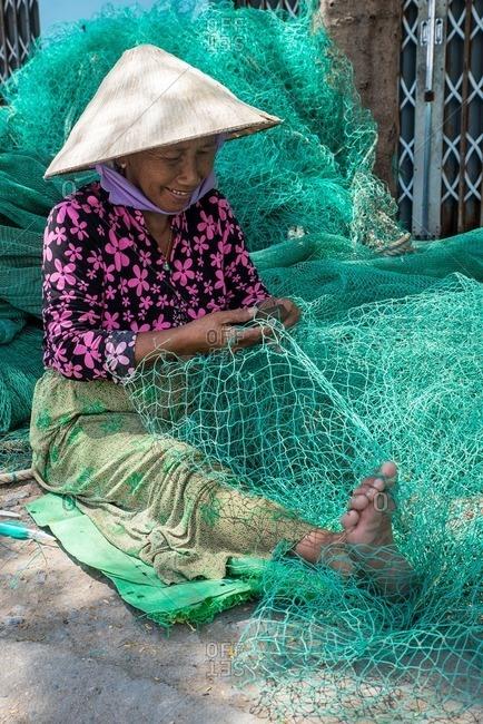 Nha Trang, Vietnam - September 6, 2016: Woman repairing fishing net