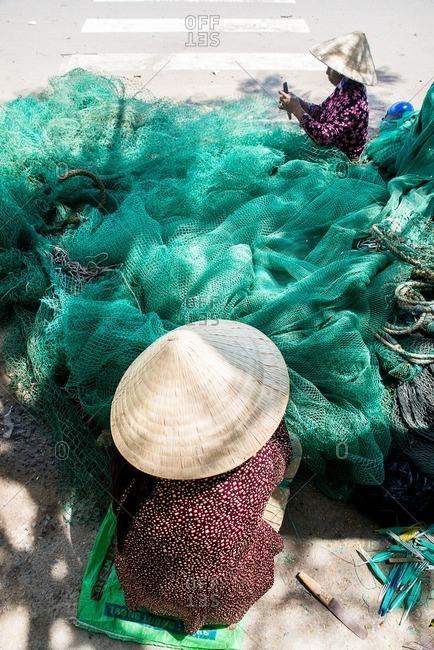 Vietnamese women stitching fishing net