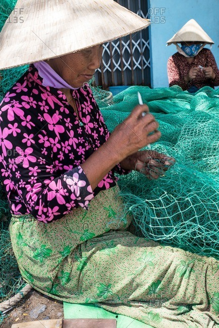 Nha Trang, Vietnam - September 6, 2016: Vietnamese women repairing fishing net