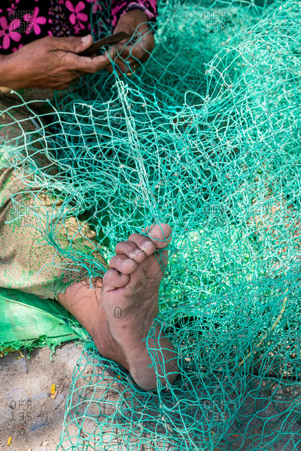 Foot of woman repairing fishing net