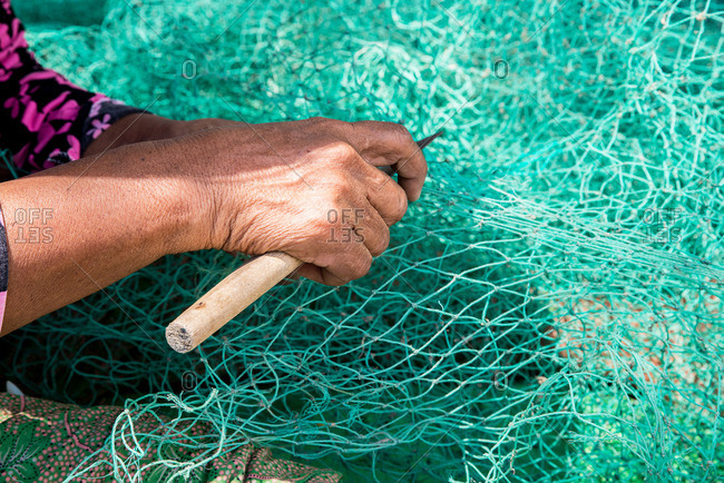Hand of woman repairing fishing net