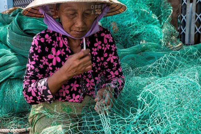 Nha Trang, Vietnam - September 6, 2016: Vietnamese woman stitching a fishing net