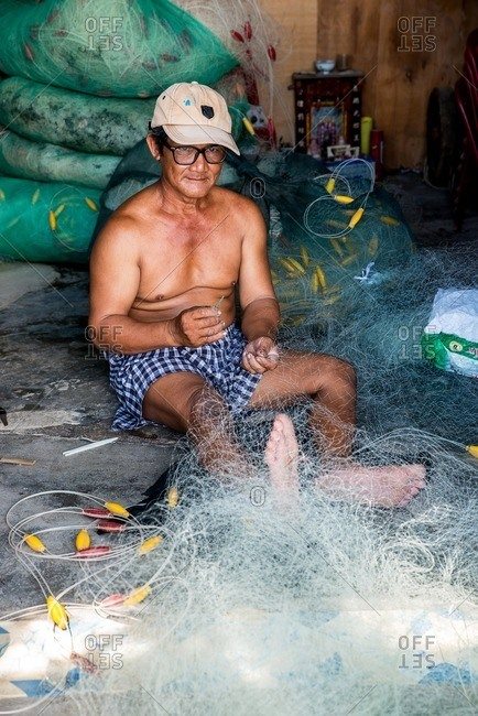 Nha Trang, Vietnam - September 6, 2016: Vietnamese man stitching fishing net