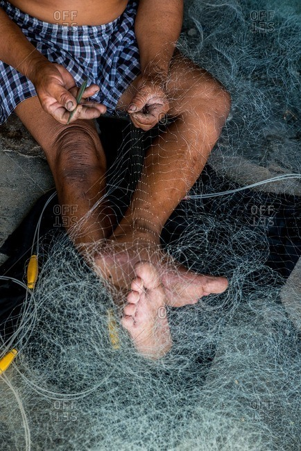 Vietnamese man stitching a fishing net