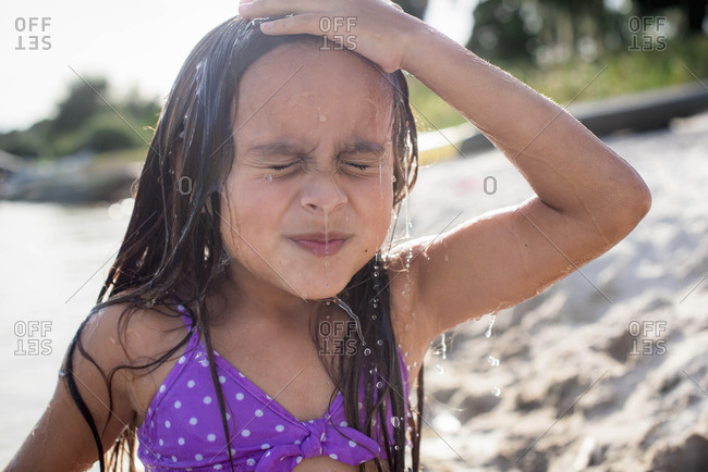 Girl at beach with water on face