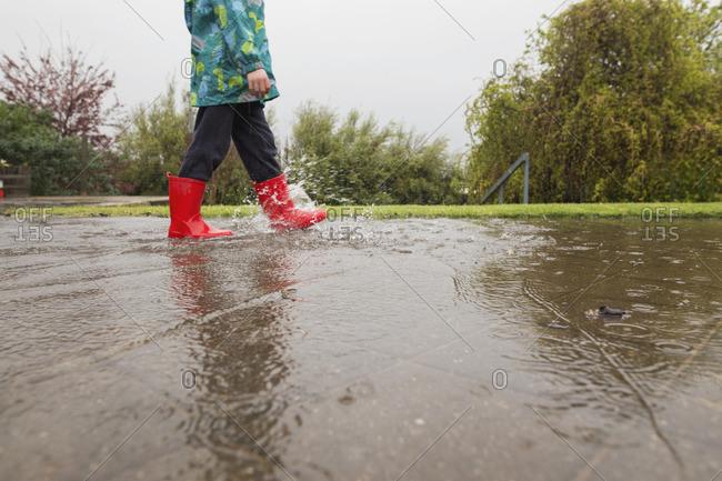 Child walking in rain water on ground