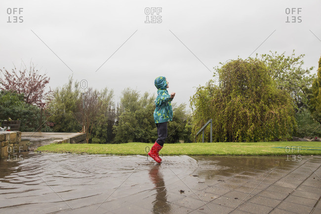 Child jumping in rain puddles