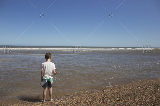 Boy standing on a pebble beach