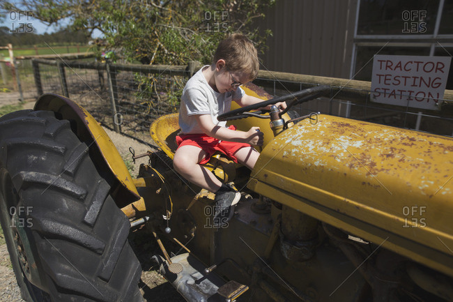 Boy pretending to drive a tractor