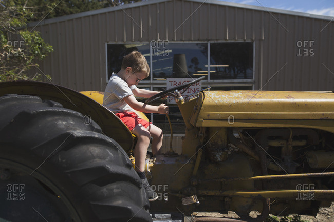 Boy pretending to ride tractor