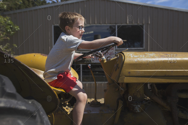 Boy pretending to ride a tractor