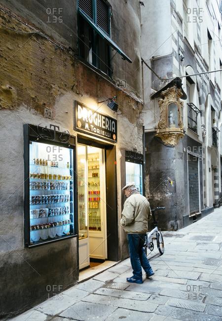 Genoa, Italy - November 24, 2014: Man looking into a store from the Via di San Bernardo in Genoa, Italy