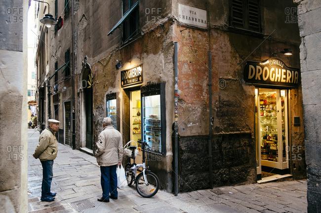 Genoa, Italy - November 24, 2014: Men talking in front of a store on the Via di San Bernardo in Genoa, Italy