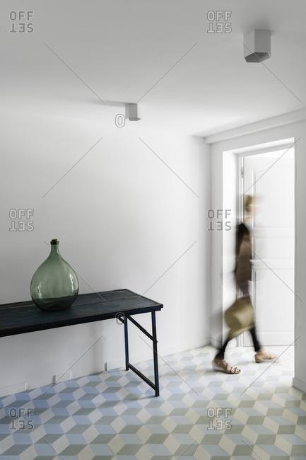 Woman walking out of a sunlit studio