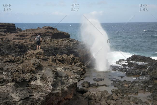 Man standing and watching the Nakalele blowhole on Maui, Hawaii