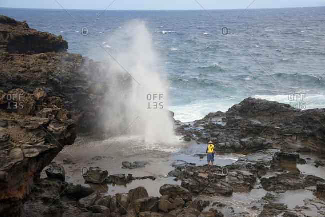 Man watching the Nakalele blowhole on Maui, Hawaii