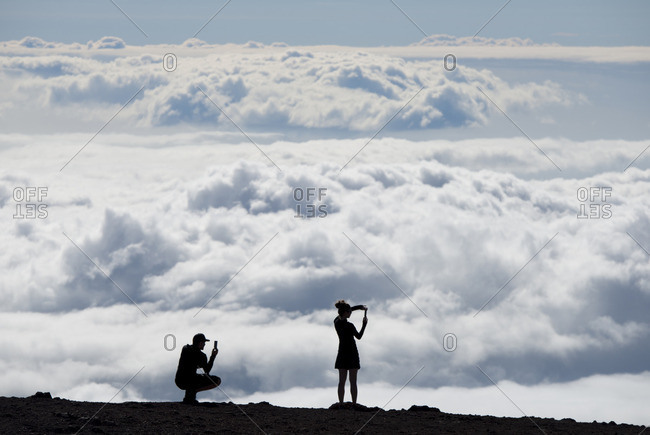 People silhouetted against the clouds at a lookout point in Haleakala National Park, Maui, Hawaii