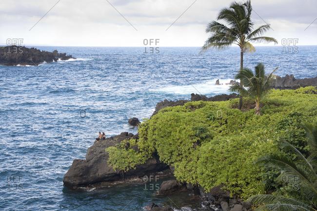 A couple sitting along the black lava coastline of Maui, Hawaii