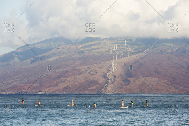 Paddle boarders and distant wind farm in Maui, Hawaii