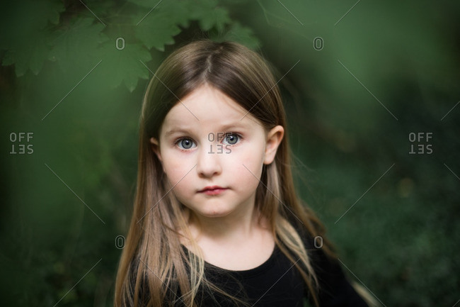 Head and shoulders portrait of a beautiful young girl in garden