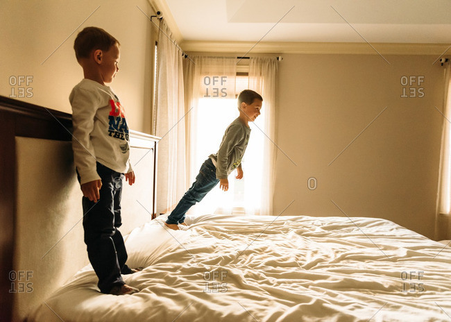 Two boys playing on big bed