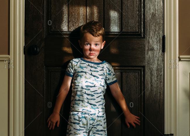 Surprised young boy standing against door