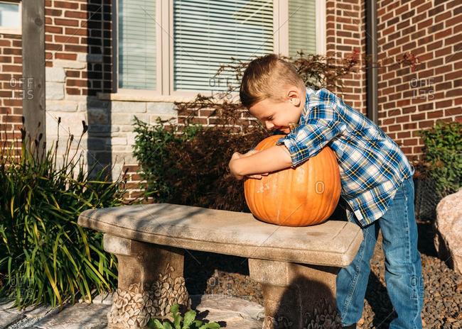 Young boy hugs his pumpkin on garden bench