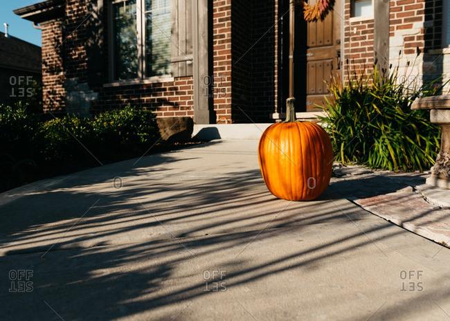 Pumpkin on front walkway of house