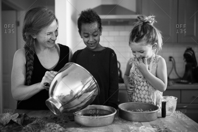 Mother with two daughters making cake at kitchen counter