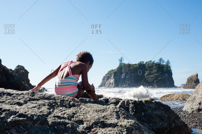 Young girl sitting on rocks