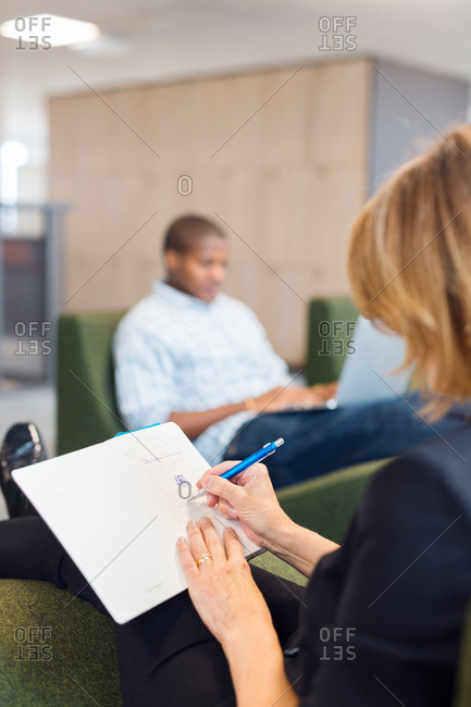 Architect writing in notebook