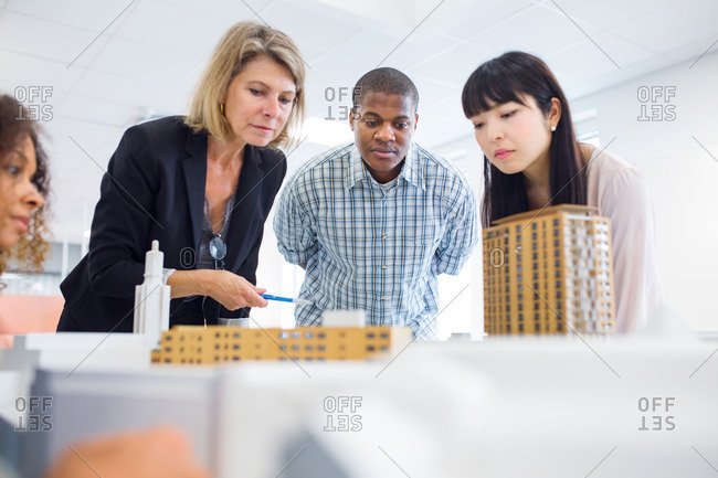 Architects looking at model in office
