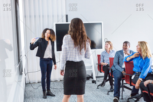 Female architects giving presentation at office meeting