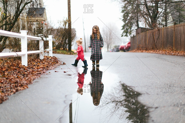 Sisters in pajamas playing in puddles