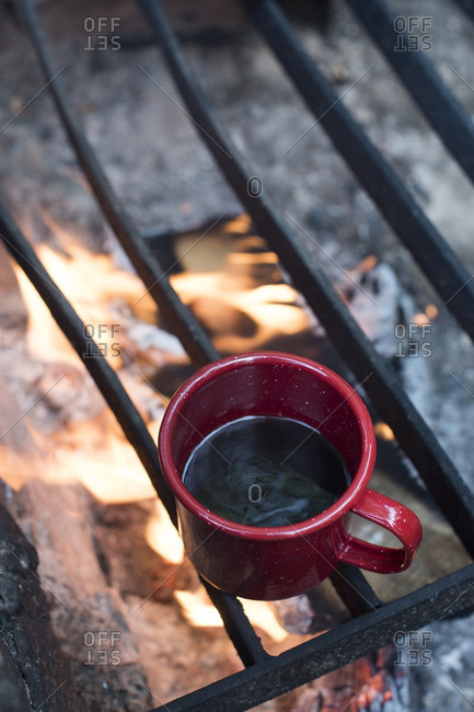 Heating cup of coffee on campfire