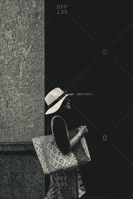 New York City, New York - February 22, 2016: Lady with a textured bag walking on Madison Avenue