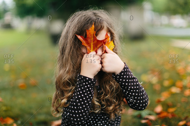 Young girl holding leaves in front of her eyes