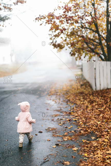 Little girl walking on a street with leaves in autumn