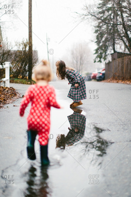 Children jumping in puddle in the street
