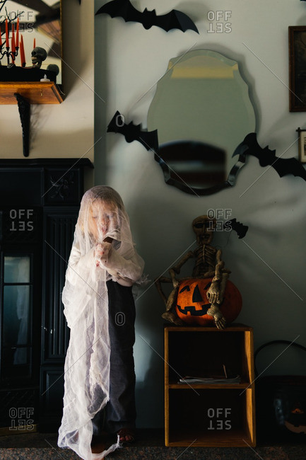 Child covered in cloth by Halloween decorations