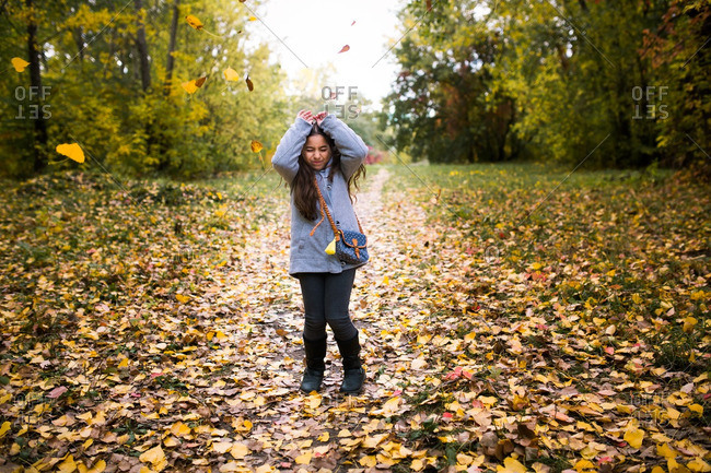 Girl throwing colorful leaves in the air in autumn