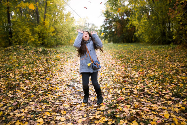 Girl throwing leaves in the air in autumn