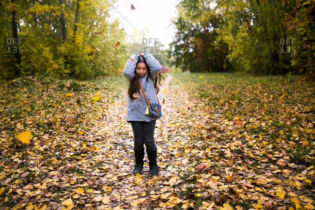 Girl covering her head while colorful leaves fall