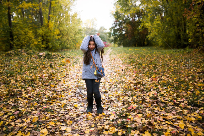 Girl covering her head while leaves fall