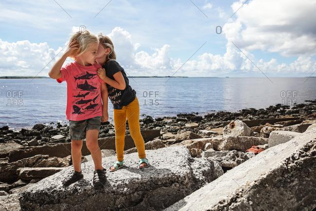 Little girl and boy telling secrets on a rocky beach