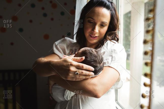 Mother admires her newborn baby near a nursery window