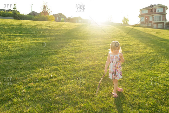 Little girl walking in grassy field with a stick