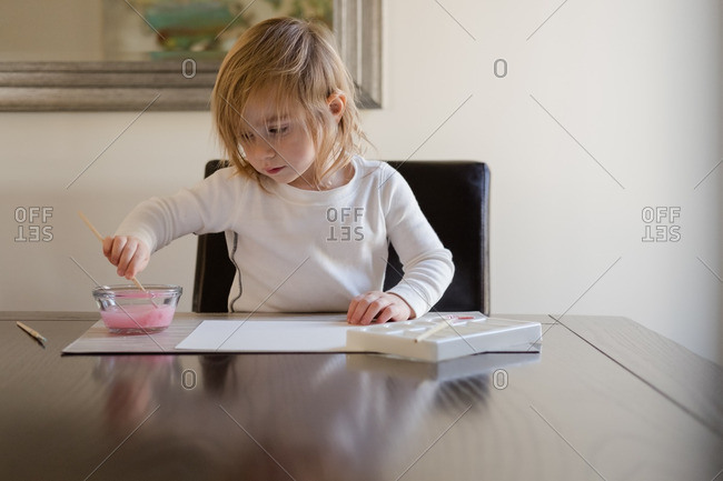 Little girl rinsing paintbrush while painting a picture at dining room table