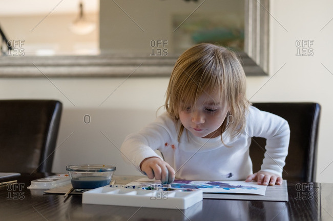 Young girl finger painting a picture at the dining room table
