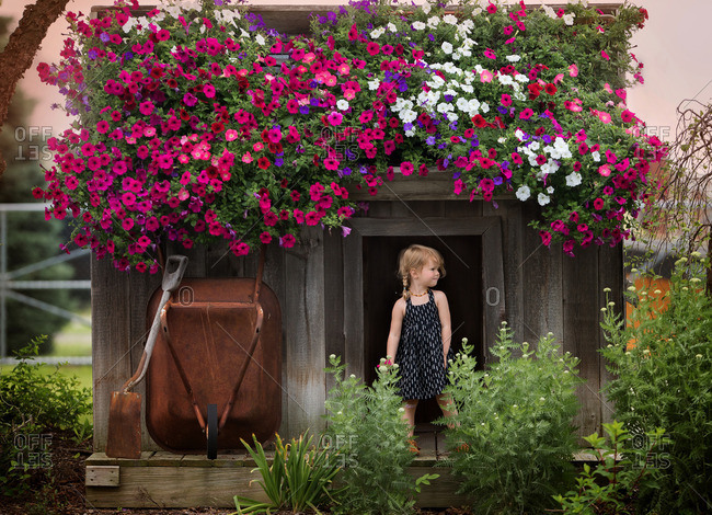 Young girl standing in doorway of shed with colorful flowers